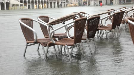 Chairs and tables in Saint Mark square during the Tide in Venice