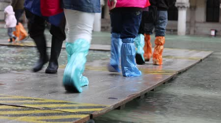 People with gaiters on the walkway during the flood in Venice