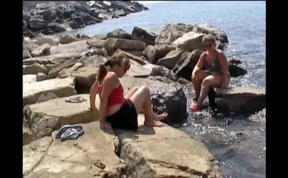 купаться : Mom and daughter sat on some rock at shoreline