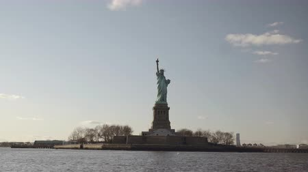 освещенный : Semi wide shot of Statue of Liberty filmed in the sunset from the river in New York, United States of America