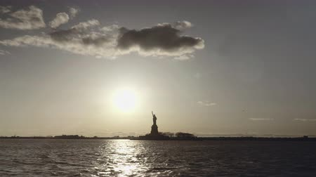 dourado : Extra wide shot of Statue of Liberty filmed in the sunset from the river in New York, United States of America