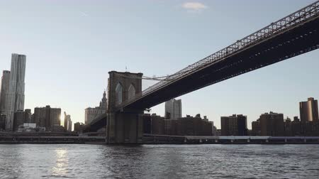 Бруклин : A view of Lower Manhattan skyline filmed from the boat in the East River under the Brooklyn Bridge in New York, United States Стоковые видеозаписи