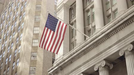 bonds : Semi side shot of American flag waving in a calm breeze off a historical financial building on the Wall Street in Lower Manhattan, New York, United States Stock Footage