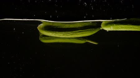 ingredienti : Fresh Cucumbers falling into water close-up slow motion