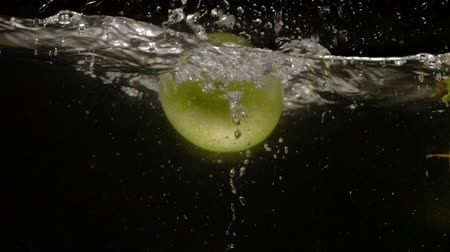 naturale : Green fresh apples are falling into water with splash on black background close-up slow motion