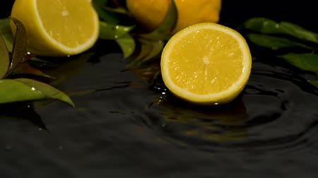 citron : Lemon slice drops on water surface with splash on black background close-up slow motion