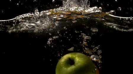ingredienti : A green apple and two oranges are falling into water on a black background close-up slow motion Stock Footage