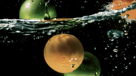 ingredienti : Fresh green apples and oranges are falling into water with splash on black background close-up slow motion Stock Footage