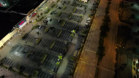 sideways : Night aerial drone over a shopping plaza parking lot