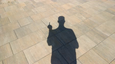 hallucination : The shadow of a man showing an obscene gesture