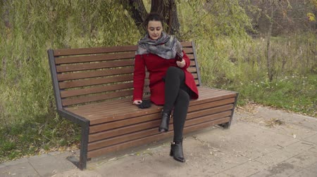 soymak : The girl sitting in the Park on a bench stealing phone