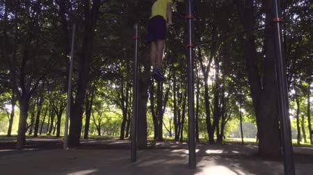 тянуть : The guy does rise with a revolution on a horizontal bar Стоковые видеозаписи