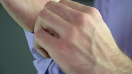 sleeve : A man unzips a button on the sleeve of his shirt Stock Footage