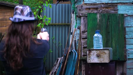 vazba : The girl in the hat shoots a gun into a bottle of water