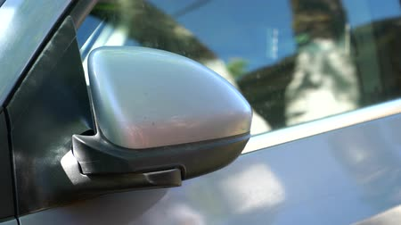 part of the frame : A man comes to the car and closes the side mirror Stock Footage