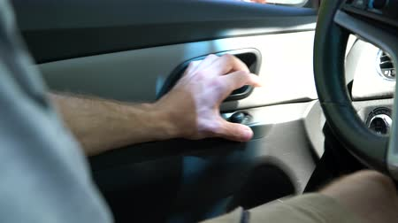A man sitting in the car pulls the door handle