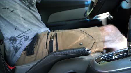 The man in the car pulls the handbrake lever Stok Video