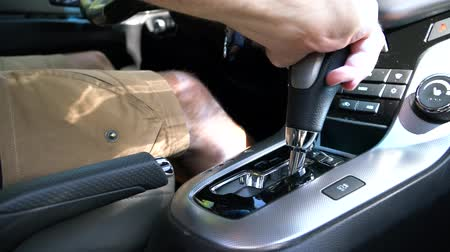 kavrama : The man switches the selector of the automatic transmission to drive mode Stok Video
