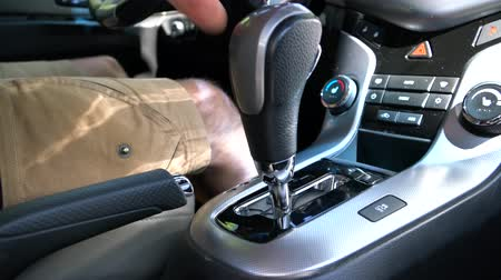 lever : A man switches the selector of the automatic transmission in Parking mode Stock Footage
