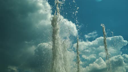 сочетание : Several jets of the fountain rising against the cloudy sky