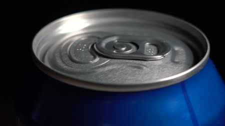 ón : The blue tin of carbonated water rotates on a black background around its axis