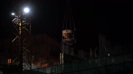 inacabado : On night construction site a crane lifts a concrete mixer