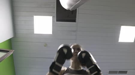 hajtások : Girl boxer strikes a Boxing bag, the camera shoots from the lower angle