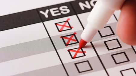 tick : Hand filling yes and no at the checklist box. Close up.