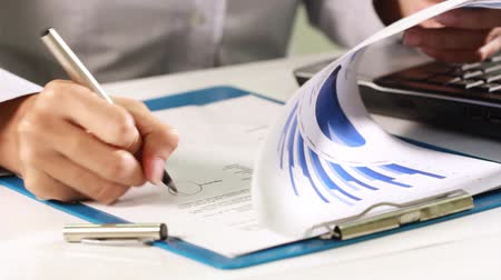 small businessman : Hand of a businesswoman correcting the worksheet gesture,  then signing it.
