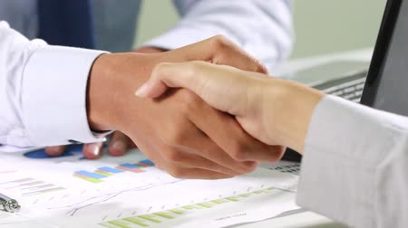 interior : Businessman reading a contract, signing  then shaking hand to a businesswoman, no face showed