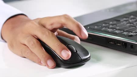 fare : closeup of a businessman using laptop is typing on the keyboard and use the mouse.
