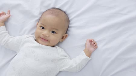 újszülött : happy baby laying on a bed