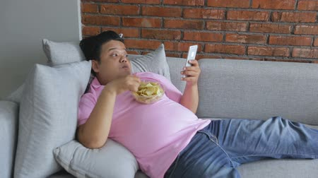 porky : lazy male having meal while using mobile phone