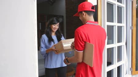 postacı : man in red uniform delivering parcel box to recipient