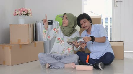 indonesian : muslim couple choosing paint for the wall Stock Footage