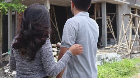 unfinished : couple with their nearly finished house Stock Footage