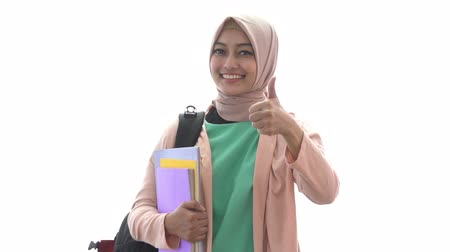 medics : beautiful medical student holding books while giving thumbs up