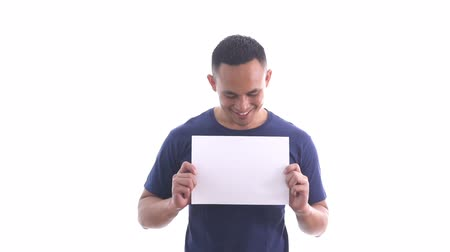 pozdravit : casual young man wearing blue shirt holding blank white paper