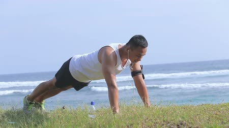 beach panorama : sporty man doing push up while listening a music