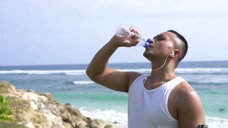 ケース : sporty young man drinking a mineral water 動画素材