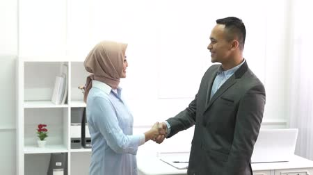 cumprimentar : businessman and business woman shaking hands at office