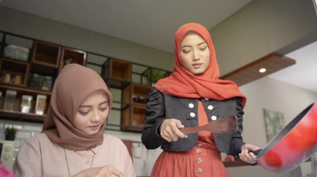 lebaran : Two woman hijab make some cuisine to serve when breaking fast