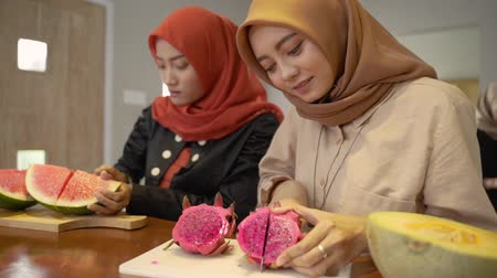 lebaran : Two asian woman hijab prepare some fruits to make cocktail