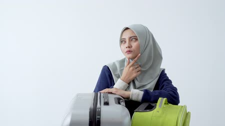 マレー語 : Asian young hijab woman with suitcase thinking hard and serious