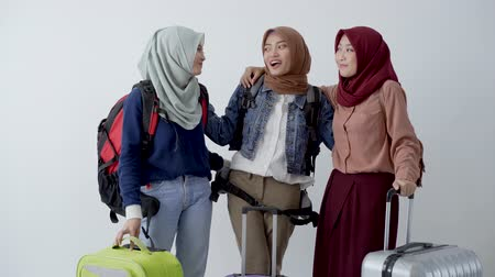 lebaran : Three hijab woman standing holding suitcase and carrying bag