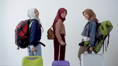 lebaran : Back view, three hijab woman standing holding suitcase and carrying bag