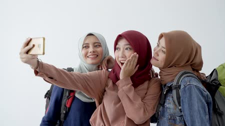 lebaran : Portrait happiness of hijab traveller selfie together with smartphone Stock Footage