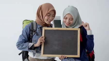 pasaport : two muslim woman backpacker with blackboard