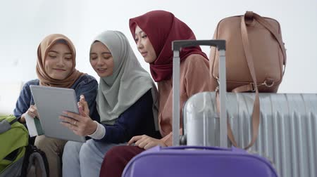 bavul : muslim asian woman friend sitting in airport terminal
