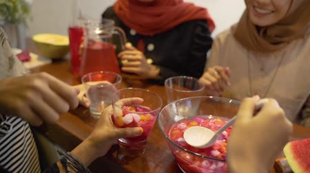 lebaran : close up of hands woman takes fruit cocktail from bowl into glass